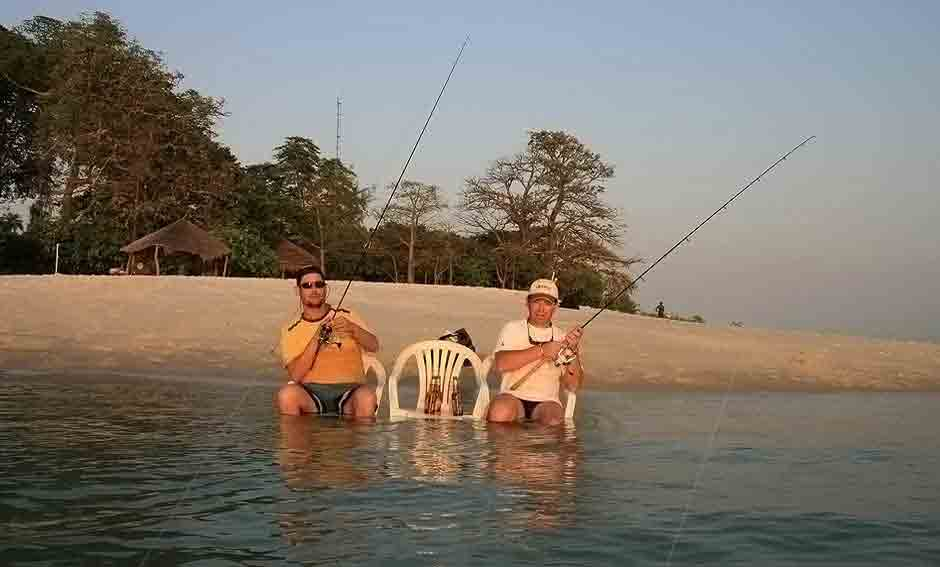 Two fishermen with feet under water holding fishing rods